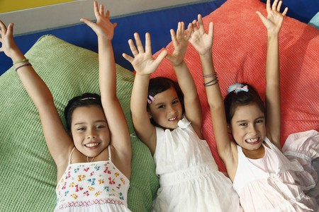 hands raised: Girls lying on pillows with their hands raised Stock Photo