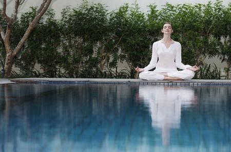 mujer meditando: Mujer meditando por el lado de la piscina