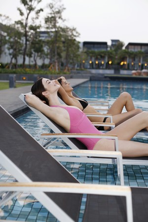 Women relaxing on lounge chairs photo