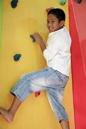 recreational climbing: Boy climbing rock wall