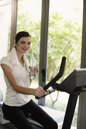 Woman holding a bottle of water while exercising in the gymnasium Stock Photo - 7534685