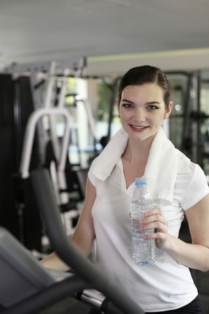 Woman holding a bottle of water while exercising in the gymnasium photo
