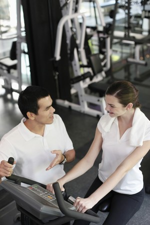 Personal trainer helping woman exercising in gymnasium Stock Photo - 7534728