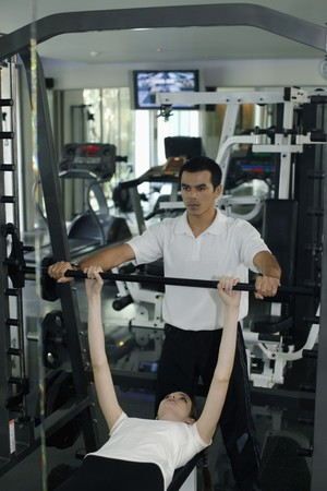 Personal trainer helping woman exercising in gymnasium Stock Photo - 7534876