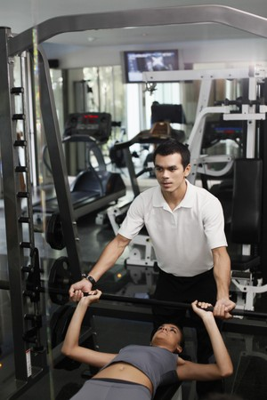 Personal trainer helping woman exercising in gymnasium Stock Photo - 7534772