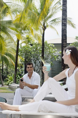 Woman with a glass of cocktail sitting on lounge chair, man text messaging in the background photo