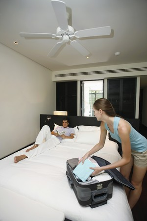 Woman unpacking her luggage, man reading book in bed photo