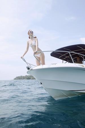 Man steering speedboat, woman standing at bow of speedboat photo