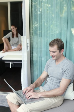 Man using laptop, woman listening to music in the background photo