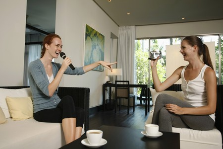 Woman singing karaoke while her friend is recording with video camera photo