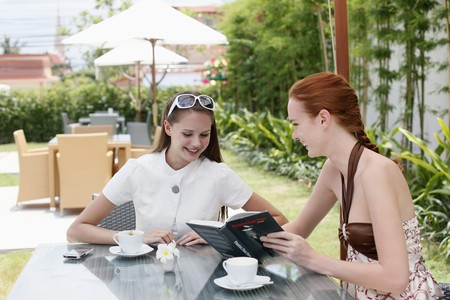 Women looking at book and smiling Stock Photo - 7595575