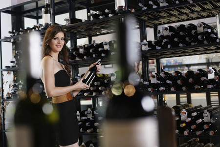 Man selecting wine bottle from rack photo