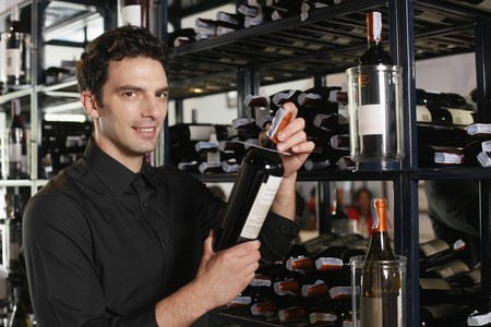 southeastern european descent: Man selecting wine bottle from rack