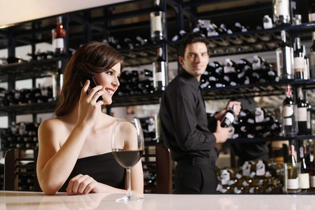 Woman talking on the phone, man selecting wine bottle in the background