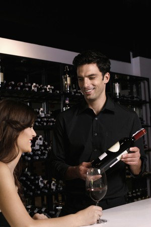 Man recommending a bottle of wine to woman photo