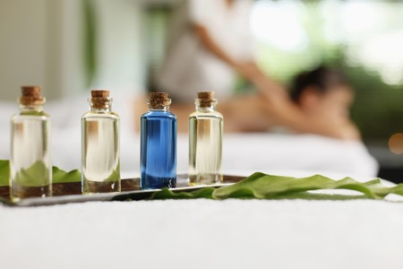 Bottles of massage oil, woman receiving back massage in the background