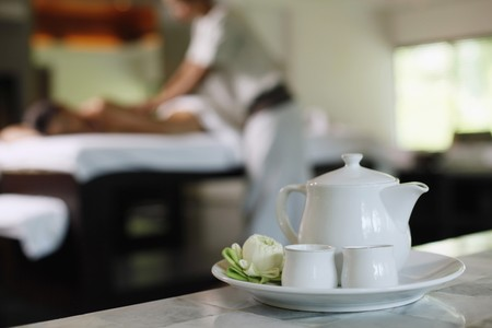 Teapot and tea cups, woman receiving massage on the background Stock Photo - 7594752