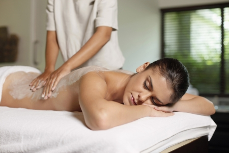 massaging: Woman receiving back massage with coconut scrub Stock Photo