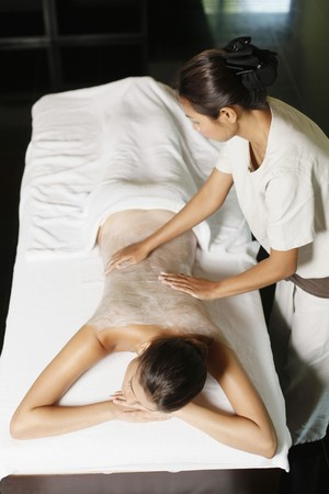 Woman receiving back massage with coconut scrub photo