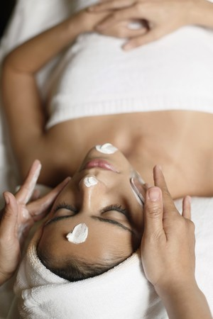 beauty therapist: Woman in health spa, having cream applied to face Stock Photo