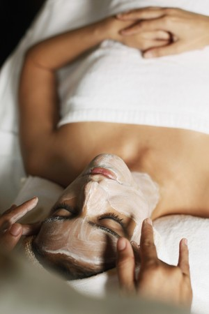 applied: Woman in health spa, having cream applied to face Stock Photo