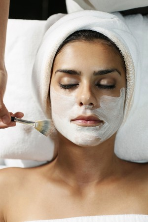 Woman having facial mask applied with brush photo