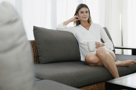 Woman sitting on couch holding a cup photo