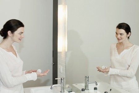 Woman holding lotion and looking at the mirror photo