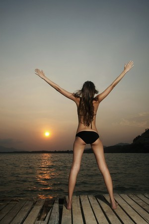 Woman standing on pier with hands raised Stock Photo - 7595502
