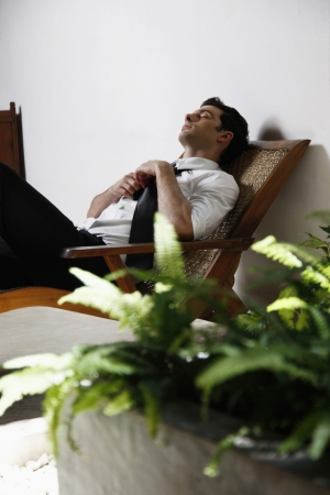 Businessman loosening his necktie while resting on lounge chair photo