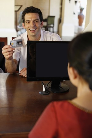 Man giving credit card at hotel reception desk photo