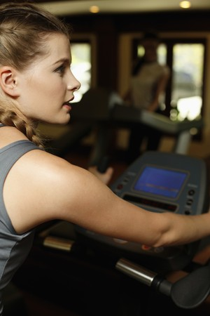 Woman on exercise bike at gym Stock Photo - 7595314