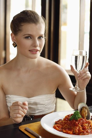 Woman holding a glass of water with seafood spaghetti on the table photo