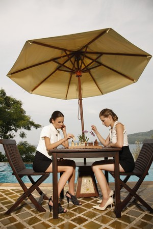 ukrainian ethnicity: Businesswomen playing chess by the poolside