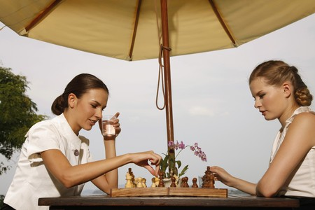 poolside: Businesswomen playing chess by the poolside