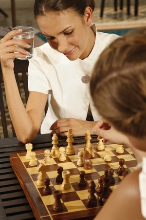 jugando ajedrez: Mujeres empresarias que jugar al ajedrez por la piscina  Foto de archivo