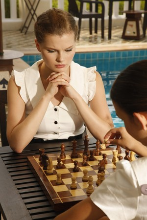 Businesswomen playing chess by the poolside photo