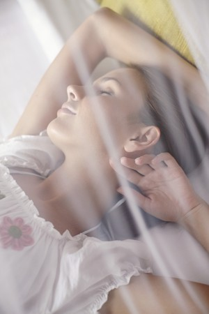Woman sleeping under mosquito netting Stock Photo - 7595335