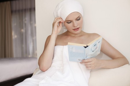 Woman wrapped in towel reading book on sofa Stock Photo - 7595023