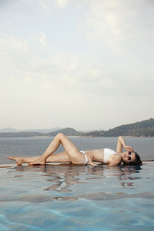 Woman lying down at the edge of pool photo