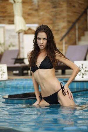 Woman in bikini posing at the pool photo