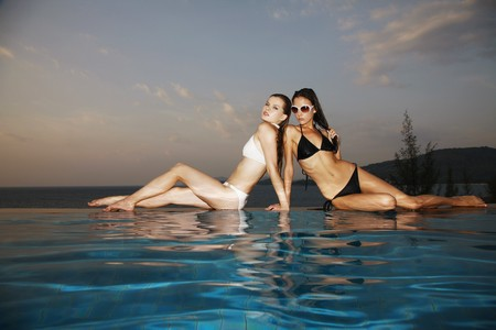 Women sitting at the edge of pool Stock Photo - 7595488