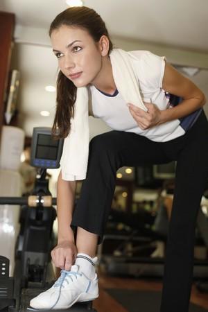 bending down: Woman bending down and adjusting her shoe