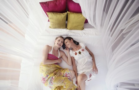Women lying on bed and talking on the phone photo