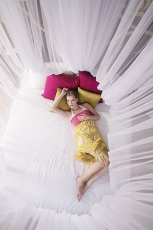 Woman on bed under mosquito netting photo