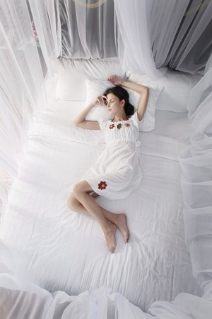 Woman sleeping under mosquito netting