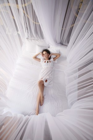 Woman lying on bed with mosquito netting photo
