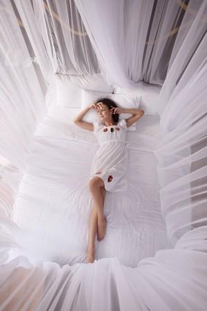 netting: Vrouw liggen op het bed met muggen netten  Stockfoto