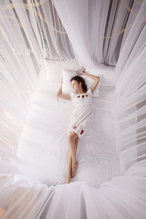 woman lying down: Woman sleeping under mosquito netting