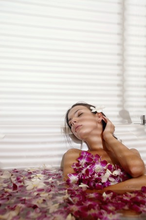 Woman relaxing in bathtub with flower petals photo